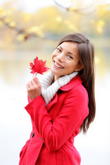 Fall girl holding red Autumn leave outside