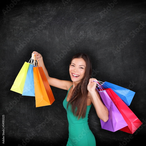 Shopping woman holding shopping bags on blackboard