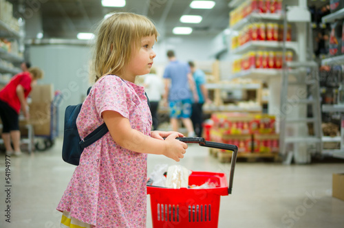 Adorable girl with backpack stay with red shopping cart in super