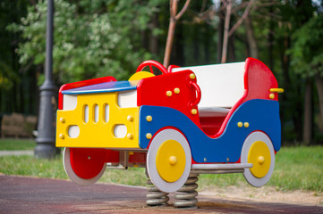 Wooden baby car on two springs on kids playground