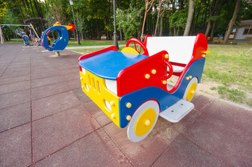 Wooden baby car and helicopter on two springs on kids playground