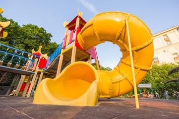 Yellow spiral baby slide on kids playground. Shot from floor lev