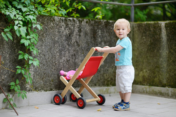 Cute little boy with his toy carriage