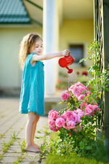 Cute little girl watering flowers
