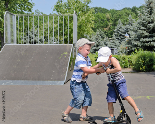 Two young boys fighting over a scooter