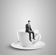 businessman sitting on cup