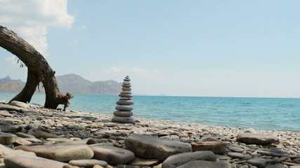 Pyramid of pebbles on sea background