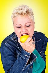 Portrait of middelaged beautiful woman eating fresh lemon