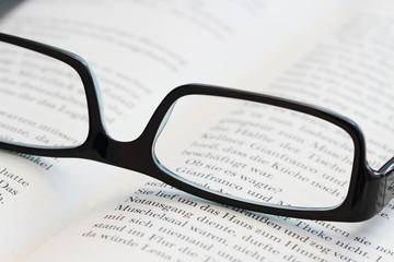 Brille mit einem offenen Buch