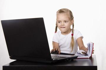 Девочка работает за ноутбуком, и записывает в блокнот