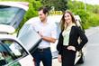 Leinwanddruck Bild - Junge Geschäftsfrau vor Taxi mit Gepäck