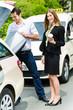 Junge Geschäftsfrau vor Taxi mit Gepäck