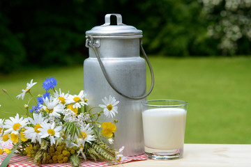 Kanne mit Milch und Blumen