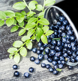 Great Fresh Blueberries in a bowl jar with big leaves on wooden