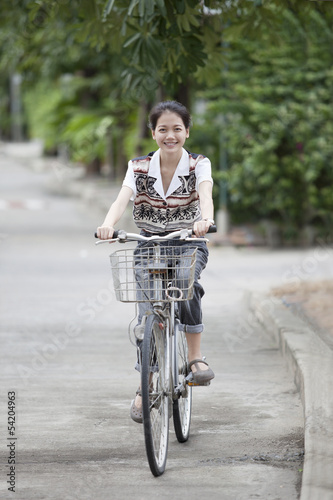 girl riding bicycle in home village street