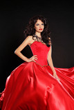Fashion model. Beautiful woman wearing in magnificent red dress