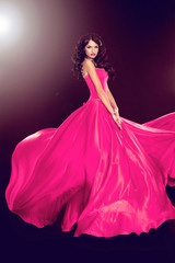 Beautiful woman in gorgeous dress isolated on black background.