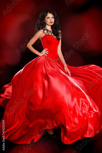 Beautiful woman wearing in magnificent red dress isolated on bla