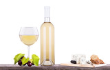 glass of white wine and a bottle with grapes