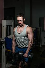 bodybuilder doing heavy weight exercise for shoulder