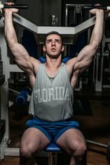 young bodybuilder doing shoulder press on machine
