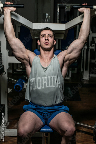 young bodybuilder doing shoulder press on machine