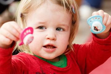 Kind spielt mit Schnullern