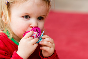 Zweijähriges Mädchen mit Schnullern