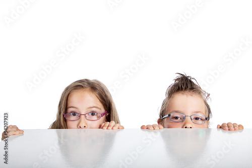 Kinder blicken neugierig über den Tisch