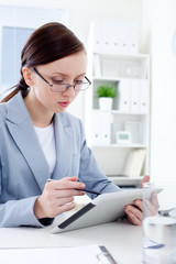 Young businesswoman reading   digital tablet