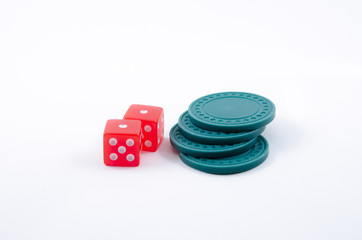 Two dice beside stack of green poker chips