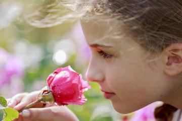 Garden - girl smelling flower in the rose garden