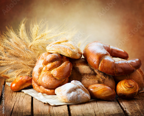 Fototapeta Bakery Bread on a Wooden Table. Various Bread and Sheaf