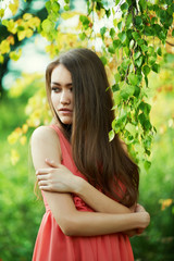 Beautiful young girl in red dress dreams in the field