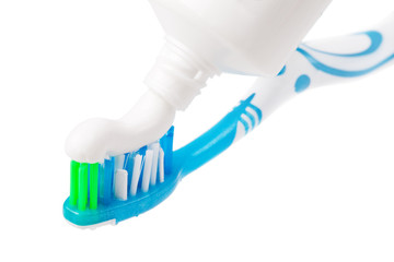 Squeezing toothpaste onto toothbrush, on a white background