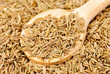 Cumin seeds macro and wooden spoon as background