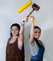 Two women posing with a roller and mallet
