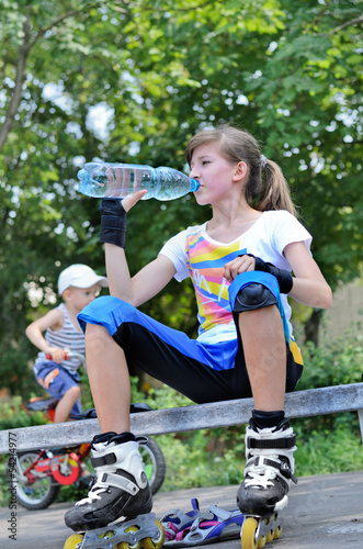 Girl pausing for a drink while roller skating