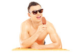 Young smiling man on a beach towel eating a chocolate ice cream