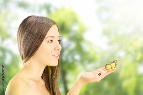 Beautiful young female holding a butterfly in a park