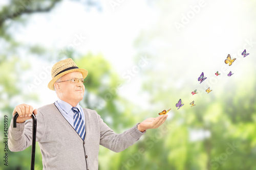 Mature smiling man holding a cane and looking at butterflies
