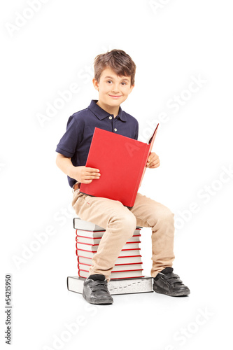 Smiling school boy sitting on a pile of books and reading
