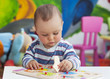 Toddler or a baby child playing with puzzle in a nursery. - 54221145