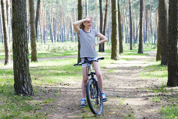 Girl with her bicycle in the forest