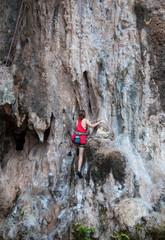 Woman climbing on the rock route summer (Railay Beach, Krabi pro