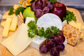 Various types of cheese and ripe grapes buffet.