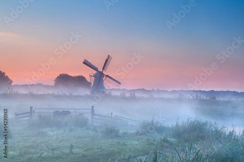 Dutch windmill in dense morning fog - 54230363