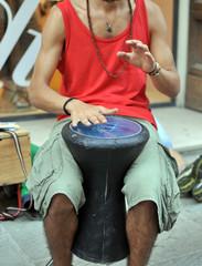 Musicista di strada suona uno darbuka, strumento a percussione