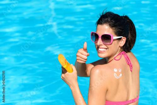 Happy woman applying sunscreen on summer