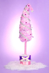Christmas tree with curved tip on lilac background
